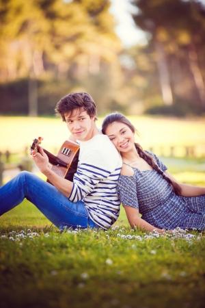 Sommerromanze mit Gitarre Junge spielt Gitarre für Mädchen