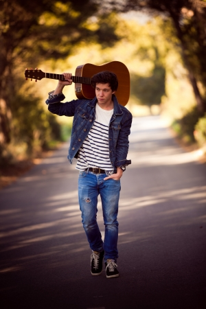 drifter, man with guitar walking outdoors photo