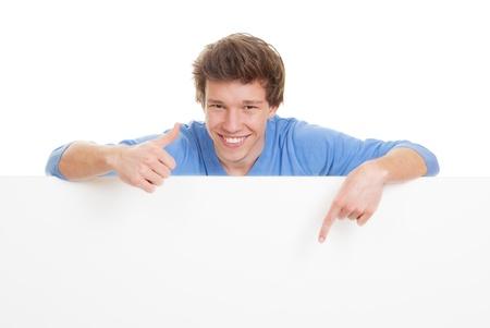 엄지가 복사 공간을 가리키는 행복 미소, 젊은 남자.