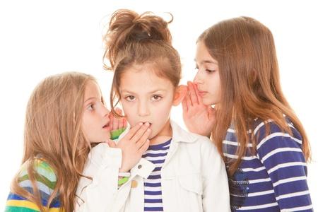 kids whispering bad news gossip scandal to shocked child Foto de archivo