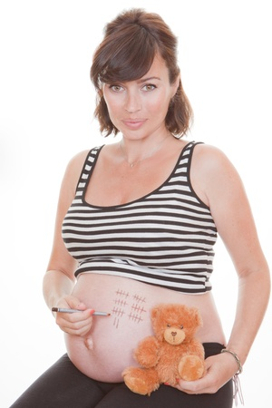 trimester: pregnant woman  counting the days off on belly Stock Photo