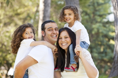 spanish girl: happy hispanic people parents giving children piggyback Stock Photo