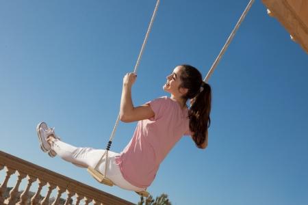 glücklich lächelnde Teenager-Mädchen auf Schaukel