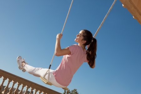 happy smiling teen girl on swing