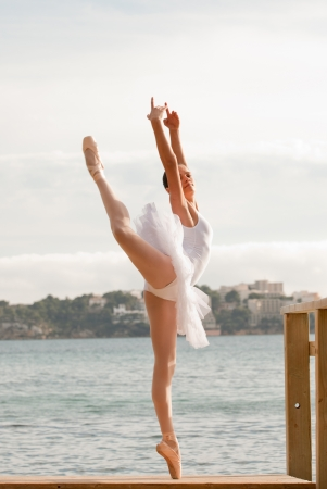 femininity: ballet dancer dancing outdoors by the sea