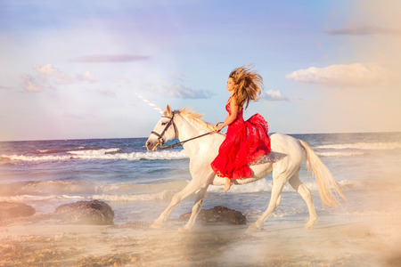 romantic woman bareback riding unicorn on beach Stock Photo