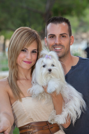 pampered pets: young couple with pet maltese dog Stock Photo