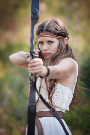 elfin: elf mythical hunter  girl shooting bow and arrow Stock Photo