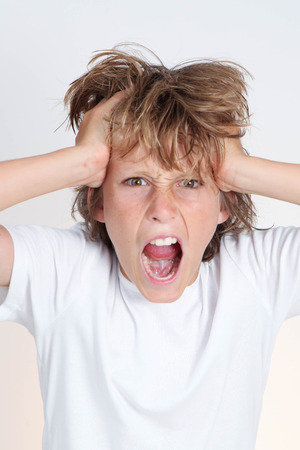 puzzlement: angry frustrated teen boy hands to head Stock Photo