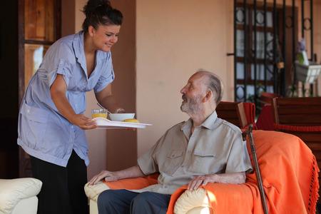 nurse or helper in residential home giving food to old senior man