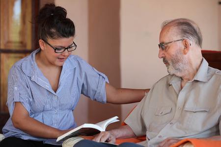 companion or granchild reading to elderly senior or grandfather