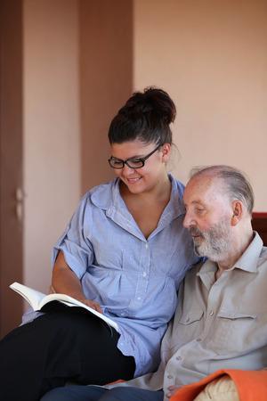persona leyendo: persona joven que lee un libro al hombre de edad avanzada