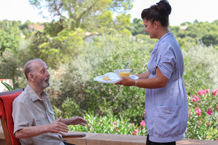 senior carers: carer giving senior healthy food in residential home Stock Photo