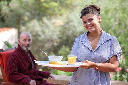 smiling home carer serving meal to elderly man Stockfoto