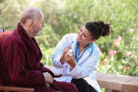 dr: smiling Dr or nurse giving medication to senior patient.