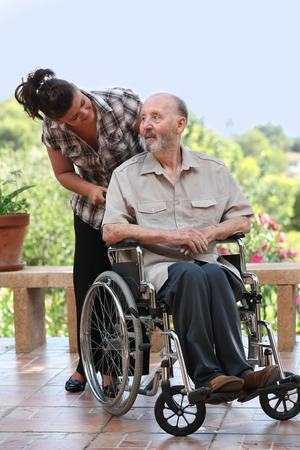 elderly man out for walk in wheelchair with grandchild Stockfoto