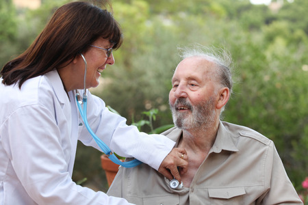 dr: dr with stethoscope checking senior patients heat beat Stock Photo