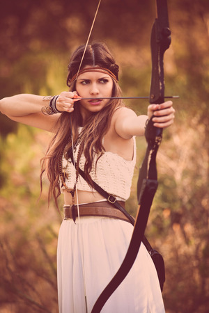 bow and arrow: woodland hunter woman with bow and arrow Stock Photo