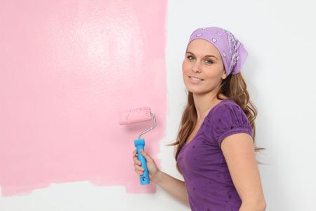 baby room: woman painting baby nursery pink