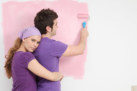 young couple painting baby nursery in new home pink photo
