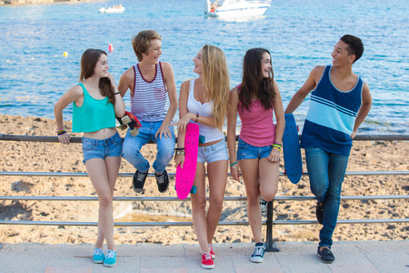 hanging woman: group of diverse mixed race teens hanging out at beach.  Stock Photo
