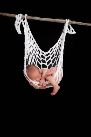 newborn baby sleeping in string hammock