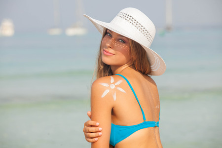Konzept für sicheren Sonnenbaden, Frau mit Sonnencreme und Hut