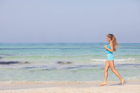 fit healthy woman jogging or running on seashore, active vacation photo