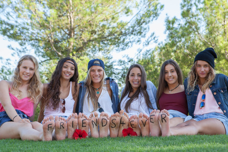 young girl feet: group of happy fashion teenagers friends wearing denim Stock Photo