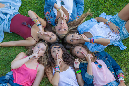 suprise: group of teens girls  fingers to lips for suprise secret.