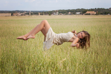 levitation: healthy woman floating in nature meadow, spa concept
