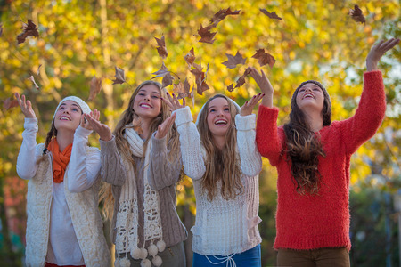 Happy teens catching leaves photo