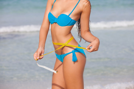 slim summer diet woman with tape measure on beach Standard-Bild