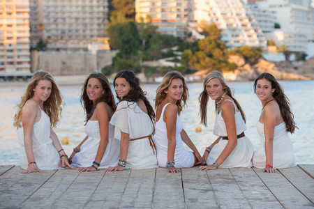group of pretty happy smiling girls dressed in white for beach party