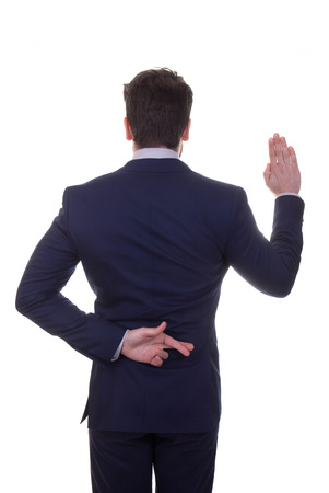 unethical: untrustworthy, lying, business man fingers crossed for luck while saying pledge. Stock Photo