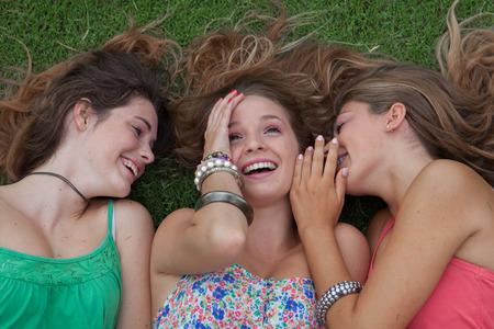 chismes: las ni�as adolescentes susurrando y chismosas secretos en vacaciones de verano Foto de archivo