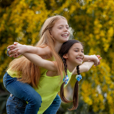 children playing outside: piggyback  happy healthy smiling summer kids Stock Photo