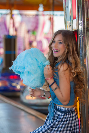 happy teen at fair eating candy floss or cotton. photo