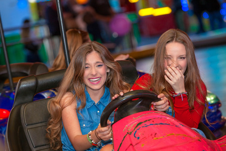 teens at fun fair riding dodgems or bumper cars.