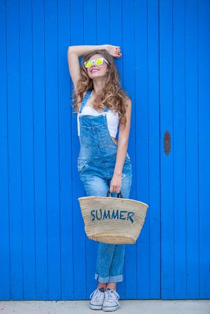summer teen girl wearing blue denim and sunglasses. Foto de archivo