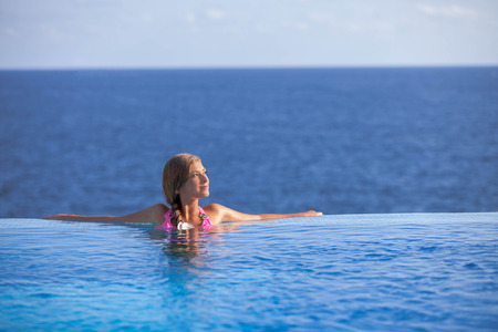 happy woman relaxing in infinity pool in summer