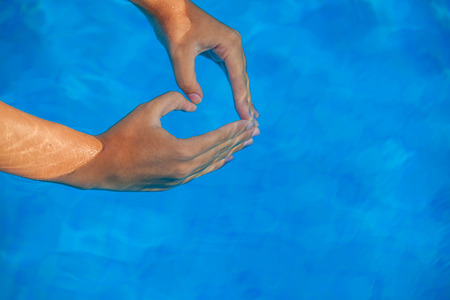 shaped hands: summer vacation love heart shaped hands in pool.