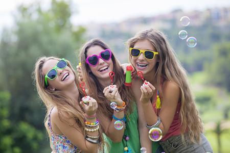 happy smiling gropu of teen girls blowing bubbles