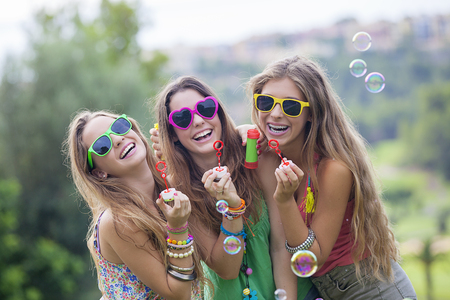 happy smiling gropu of teen girls blowing bubbles