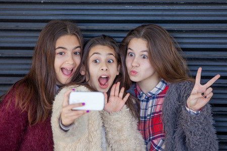 fun kids selfie with cell smart or mobile phone Stock Photo