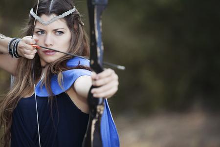arco y flecha: Archer de sexo femenino con el arco y la flecha.