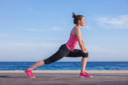 jogger: woman runner or jogger stretching exercise Stock Photo