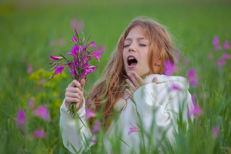 with pollen: child sneezing allergic to flower pollen in summer