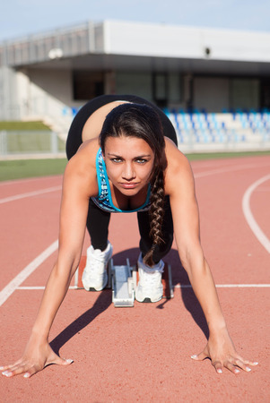woman athlete at starter at running track