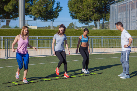 outdoor training: outdoor  fitness class group with trainer Stock Photo
